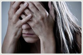 depressed woman covering her face with hands