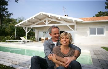 Couple Sitting in Front of Pool Behind Their House