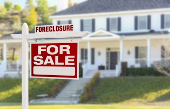 Foreclosue Sign on Top of For Sale Sign in Front of House